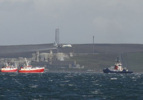 A Hercules aircraft spraying dispersants while fishing boats and a Sullom Voe harbour tug pretent to deploying booms - Photo: Hans J Marter, Shetland News