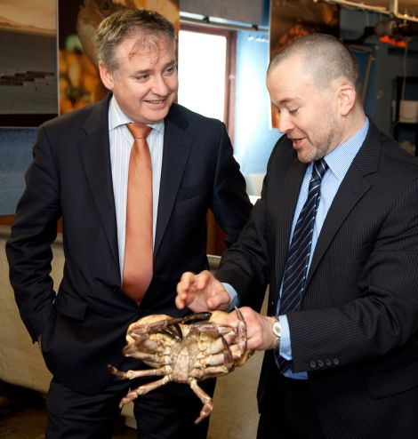 Fisheries secretary Richard Lochhead (left) invites NAFC Marine Centre's head of fisheries science Dr Martin Robinson to show him just how hard a crab can grip someone's finger. Pic. Billy Fox