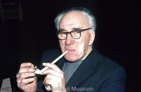 Tom Henderson smokes a pipe from the Kennemerland Photo Shetland Museum and Archives