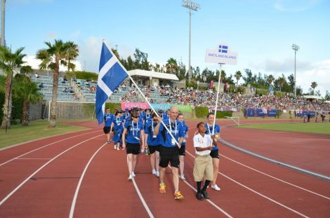 Runner Karl Simpson, swimmer Andrea Strachan and keen cyclist Aaron, aged nine from Bermuda, lead Team Shetland out into the National Stadium for the opening ceremoiny on Saturday evening. Photo Andrew Inkster