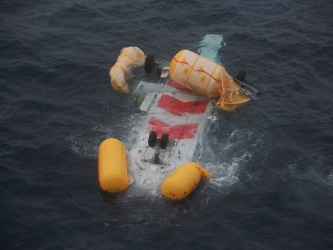 The upturned helicopter floating in the sea - Photo: Peter Hutchison/ShetNews
