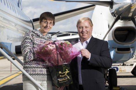 Loganair chief executive Stewart Adams presenting the Saab 2000's first paying customer, Shetland-based doctor Aileen Brown, with flowers and a flights voucher.