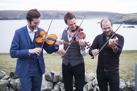 Nordic Fiddlers' Bloc, featuring Shetlander Kevin Henderson (centre), enjoying the fresh Fetlar air ahead of their Friday night concert. Photo: Floortje Robertson