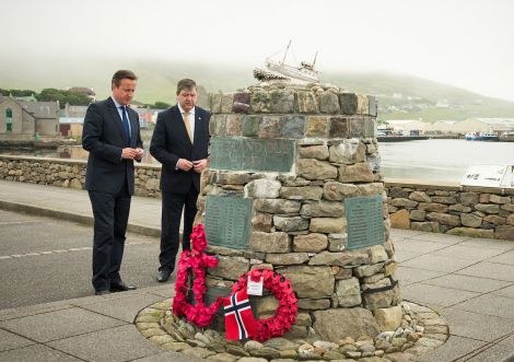 Cameron laying a wreath at the Shetland Bus memorial in Scalloway on Wednesday morning, as MP Alistair Carmichael looks on.