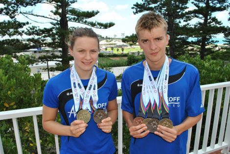 Swimmers Andrea Strachan and Felix Gifford with their haul of medals in Bermuda in 2013. Photo courtesy of SIGA