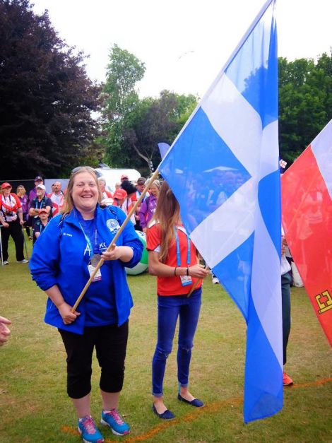 Silver medal winning hammer thrower Elaine Park can't take the grin off her face as she wields the Shetland flag at the closing ceremony in Jersey. Photo: Shetland Island Games Association