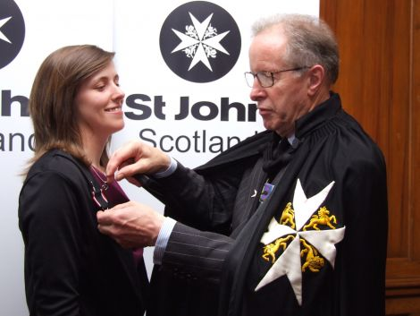 Jessica being presented with her award from Major General Mark Strudwick, Prior of St John Scotland.