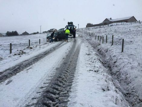 A tractor comes to the aid of a car after it slides off the road in Aith. Photo: Lewis Fraser