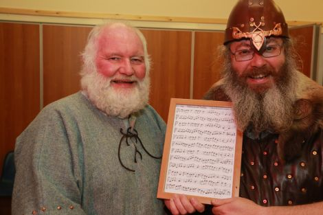 Squad member Peter Sinclair hands over the music for his freshly composed tune Thorir Hund's Two Step to a happy jarl. Photo Gordon Stove