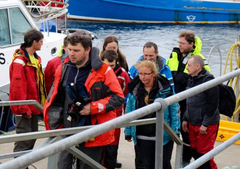 The Polish crew rescued from the yacht Miracle come ashore at Scalloway on Thursday evening, nine hours after escaping their blazing craft. Photo Chris Cope/Shetnews
