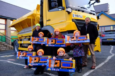 Councillors Steven Coutts (left) and Michael Stout (right) with the six pupils who chose the winning names for the gritters - Photo: SIC