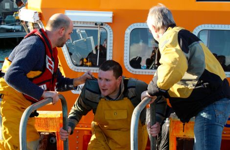 One of the Ocean Way fishermen being taken to safety at Lerwick Harbour on Friday morning - Photo: Chris Cope/Shetland News