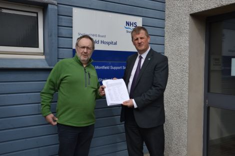 NHS Shetland chief executive Ralph Roberts (right) receiving a paper petition with over 500 signatures from Bob Birchall. Photo: Shetland News