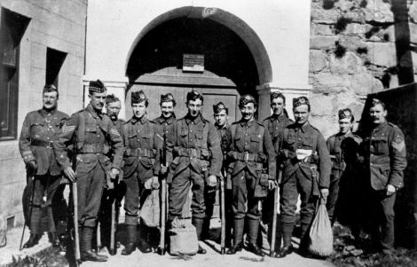The local unit of army reservists were mobilised for full-time war duty in August 1914.  The next year, as military losses on the western front increased, the Shetland Gordon Highlanders left for mainland army bases, then moved onward to France.  Here, a group are seen at the gate of Fort Charlotte on the day they left on the troopship at Lerwick, and later the whole unit is assembled at a base in mainland Britain. Photo: Courtesy of Shetland Museum.