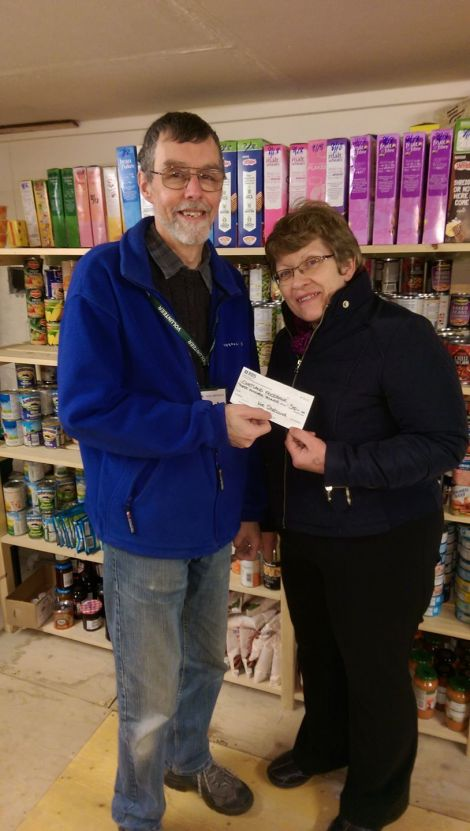 Andrea Manson of Wir Shetland presenting a cheque to David Grieve of the Shetland Foodbank.