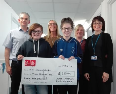 Katie Anderson and Aimee Laurenson handing over a cheque to NHS staff.