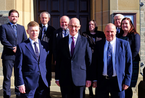 SIC top brass with John Swinney (front centre). Back row (L-R): Councillors Ryan Thomson, Allison Duncan, Alastair Cooper, Emma Macdonald and Theo Smith with chief executive Maggie Sandison. Front row (L-R): Convener Malcolm Bell, Swinney and councillor George Smith. Photo: SIC